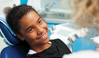 A smiling child sitting through a dental examination.